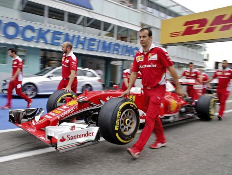 Els mecànics de Ferrari empenyent el cotxe, ahir EFE
