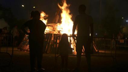 Gent al costat d'una foguera de Sant Joan en una imatge d'arxiu