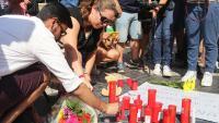 Dues persones encenen una espelma l'endemà de l'atemptat a la Rambla del 2017