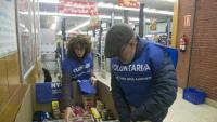 Voluntaris col·locant el menjar que els clients donen en sortir del supermercat