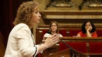 La consellera de Justícia, Ester Capella, intervenint des del faristol del Parlament sobre el decret d'habitatge amb les diputades dels comuns al darrere desenfocades