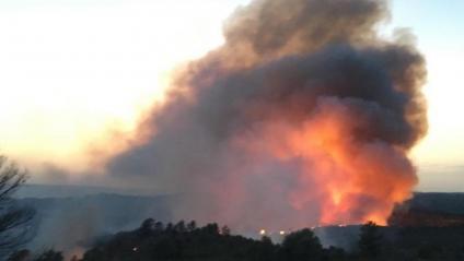 Un hidroavió sobrevola la columna de fum i, a la dreta, les flames seguien cremant entrada la nit.