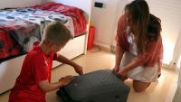 El Dídac Urbano, un dels participants de les colònies per germans de nens amb càncer que organitza l'AECC, fent la maleta amb la seva mare