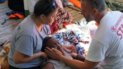 Dos sanitaris atenen els migrants a bord de l'Open Arms