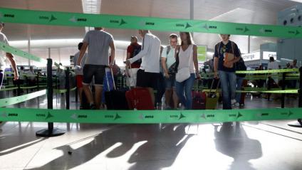Passatgers avancen per les cintes de la terminal 1 de l'aeroport del Prat