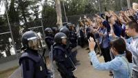Votants amb les mans enlaire davant la policia, a Lleida, el Primer d'Octubre
