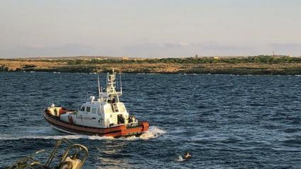 Alguns dels immigrants que ahir van saltar a l'aigua, al costat d'un vaixell de la guàrdia de costes italiana