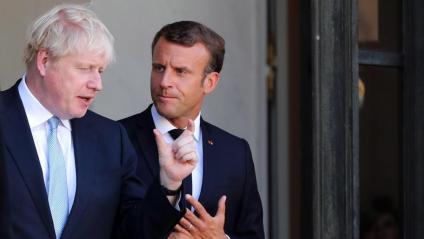 Boris Johnson parlant amb Macron, mentre abandonava ahir el Palau de l'Elisi