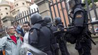 Un veí davant d'un grup d'antiavalots  de la policia espanyola, en una escola de Barcelona l'1-O del 2017