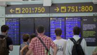Gent mirant pantalles d'informació a l'Aeroport del Prat