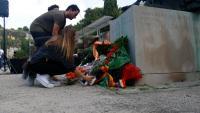 Diverses persones posen flors als peus del monument dedicat als Immolats per la Llibertat, a Montjuïc