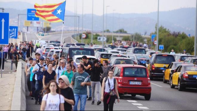 Gent caminant per l'autovia de Castelldefels en direcció a l'Aeroport després de la suspensió dels serveis de Renfe i el Metro