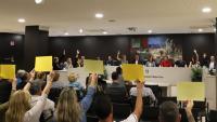Els vots favorables a Platja d'Aro, entre pancartes del públic independentista criticant la neutralitat dels altres grups