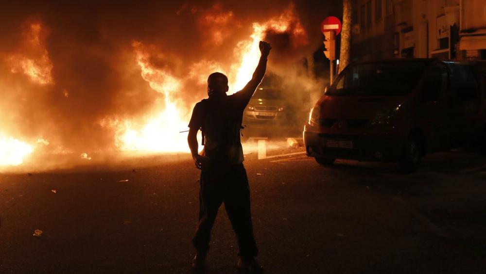 Una persona davant d'un foc prop de la conselleria d'Interior