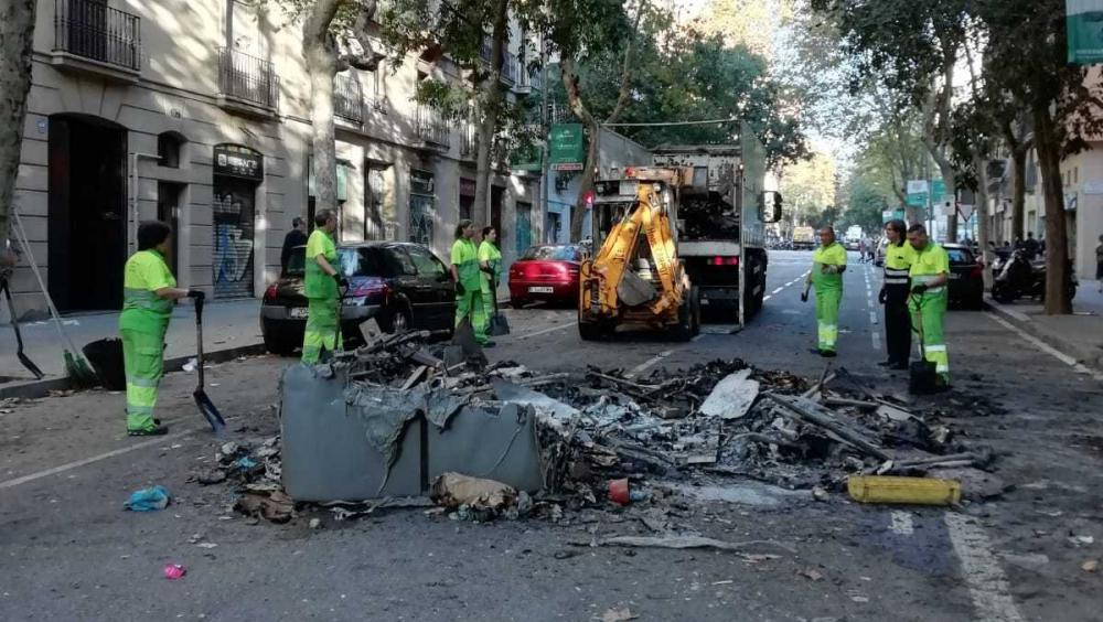 Operaris netegen al carrer Consell de Cent un contenidor cremat