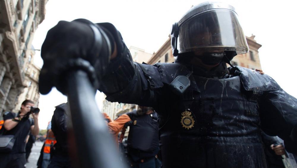 Un agent de la Policia Nacional aparta amb la porra un periodista