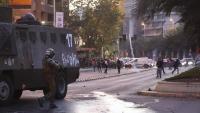 Un carabiner  apunta contra un manifestant en el marc de les protestes contra la pujada del preu del bitllet de metro, divendres
