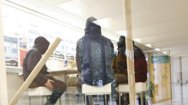 Imatge d'una porta tancada a la universitat i estudiants a l'interior