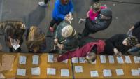 Un grup de persones tria les paperetes electorals d'una taula a les últimes eleccions generals