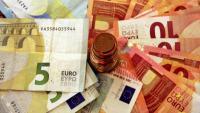 Una pila de bitllets amb una torre de monedes d'euro al centre