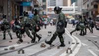 Agents antiavalots apleguen llambordes arrencades per manifestants, dijous a Hong Kong