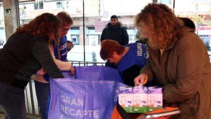 Voluntaris en un supermercat col·locant els aliments donats