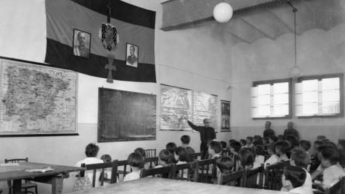 Una escola amb l'habitual iconografia franquista, amb l'àliga i els retrats del dictador i del fundador de la Falange
