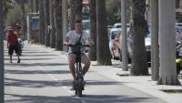 Un turista amb un patinet a motor per un carril bici del front marítim de Barcelona