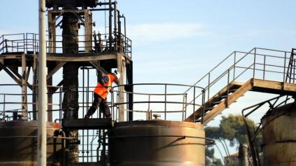 Un operari a sobre d'un dels bidons que es va cremar en l'incendi de la fàbrica de Montornès