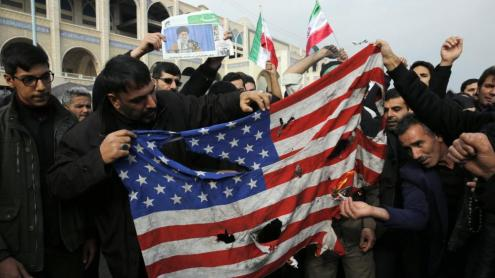 Uns homes cremen una bandera nord-americana