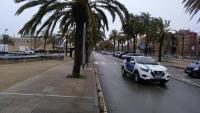 El cotxe de la policia local patrullant ahir a la tarda pel passeig marítim, on quedaven alguns cotxes aparcats