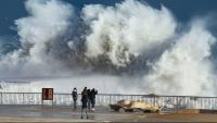 Diverses persones fotografiant onades a la Barceloneta