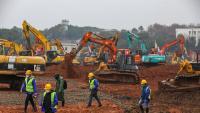 Un munt d'excavadores i personal treballant en la construcció d'un hospital a Wuhan, que estarà fet en deu dies i on es tractarà els afectats pel nou virus
