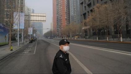 Un guarda de seguretat amb mascareta  per por del contagi del virus, ahir en un carrer desert de Pequín. Les autoritats recomanen evitar concentracions
