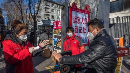 Voluntaris repartint màscares protectores, ahir a Pequín