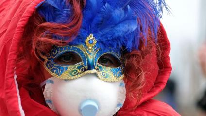 Una persona amb una màscara festiva i una altra de protecció pel coronavirus, ahir, al carnaval de Venècia abans que se n'anunciés la suspensió