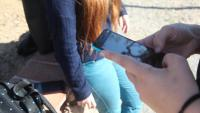 Adolescent amb un mòbil en un institut