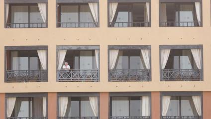 Una persona, en un balcó de l'hotel d'Adeje on es va hostatjar el metge italià amb coronavirus i on hi ha un miler de persones confinades