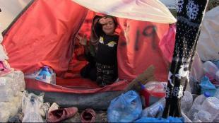 Una nena refugiada al camp de Moria saluda des de la seva precària tenda de campanya, a l'illa de Lesbos, on malviuen afganesos i sirians