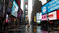 Un home camina per Times Square, a Nova York, desert a causa de la pandèmia del coronavirus