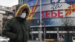 Un home amb una mascareta protectora camina per davant de l'oficina de la UE, engalanada amb banderes de Macedònia del Nord, a Skopje, dimarts