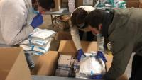 Diverses persones empaqueten material sanitari per enviar des del Departament de Treball, Afers Socials i Famílies