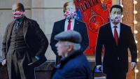 Un home passa per davant de tres figures de cartró de Vladímir Lenin, Donald Trump i Xi Jinping a Moscou