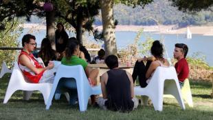 Un grup de joves conversa mentre esmorzen al BioRitme Festival amb el Pantà de Sau de fons