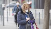 Una dona mirant el mòbil al carrer
