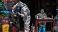 Un metge fa la prova per detectar símptomes de la Covid-19 al mig del carrer a la ciutat de Wuhan, origen de la pandèmia del virus