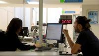 Una treballadora del SOC i un home conversen en un dels punts d'atenció del Servei d'Ocupació de Catalunya