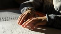 Pla detall d'unes mans llegint Braille