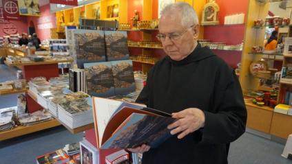 El monjo Bernabé Dalmau fullejant el seu llibre a la botiga de Montserrat