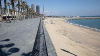 La platja de la Barceloneta ahir al migdia, buida del tot, com el passeig marítim que discorre elevat